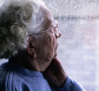 Elderly woman looking out of a window. Image credit: Thinkstock