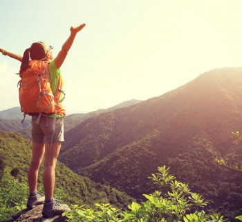 Woman opening her arms up in happiness on top of a mountain. Image credit: Thinkstock