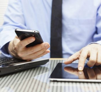 Man working on laptop, tablet and smartphone. Image credit: Thinkstock