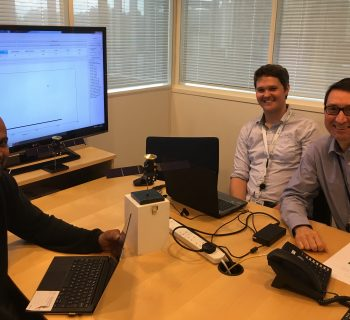 Three OU scientists in front of a computer screen