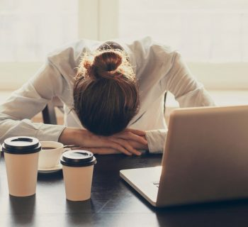 Business woman resting her head on her desk. Image credit: Thinkstock