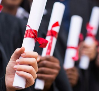 Row of university graduates holding their scrolls. Image: Thinkstock