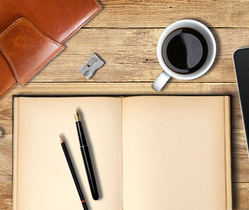A notebook, iPad and a cup of coffee