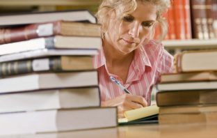 Mature female student with books in library