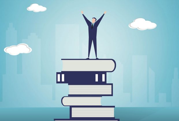 Business man standing on books, reaching for the sky. Image credit: Thinkstock