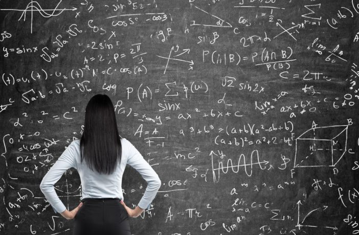 Rear view of a thoughtful woman who tries to solve math problems. Math calculations on black chalk board. Thinkstock