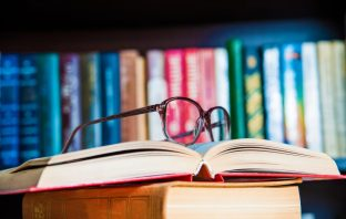 glasses and book on background bookcase close up. Thinkstock