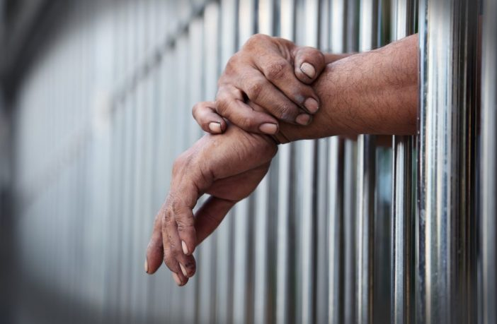 Photo of hands through prison bars