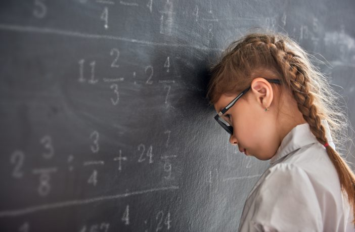 Girl holding head against a school blackboard