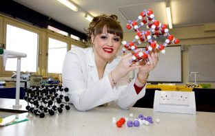 Amy King holding a model of a molecule