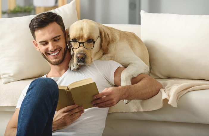 Man reading a book with a dog