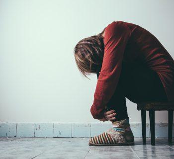 Woman slumped alone on a stool