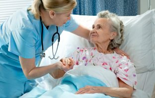 Photo of nurse caring for elderly lady in hospital bed