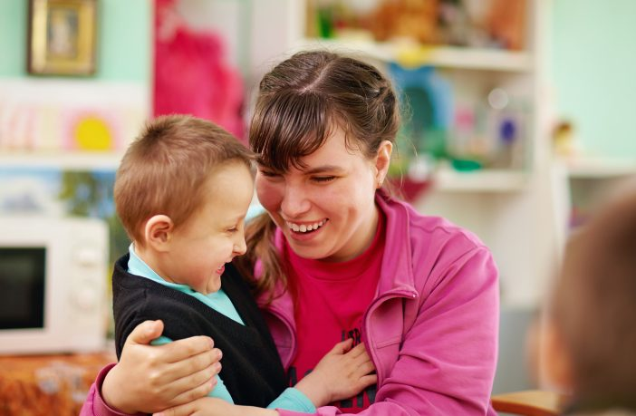 Girl with learning disability hugging child