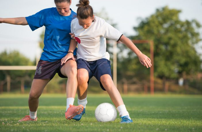 Two women tackling for a football