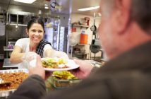 Photo of volunteer serving food in homeless shelter