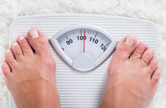 Feet of female - obese - on weighing scales