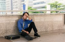 Depressed man sitting on bridge in a smart shirt