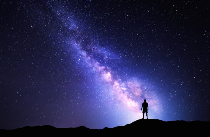 Photograph with background of Milky Way and silhouette of person