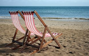 Photograph of two deckchairs on a beach