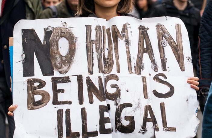 Woman holding sign saying No Human Being is Illegal