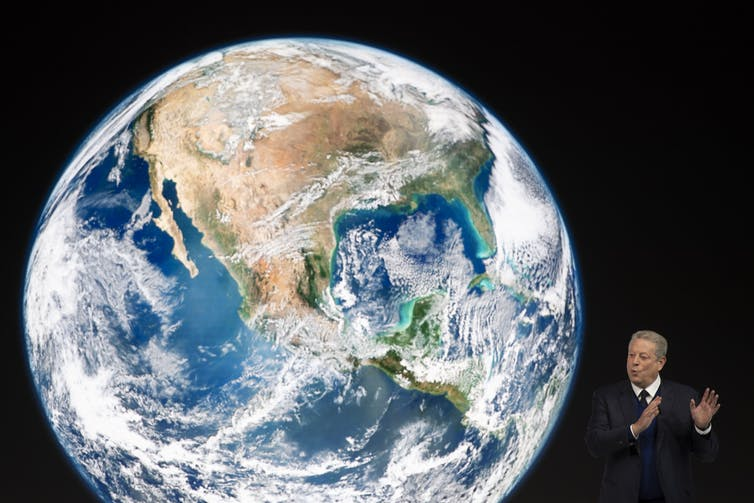 Al Gore presents in front of an image of earth