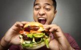 Man eating a huge burger