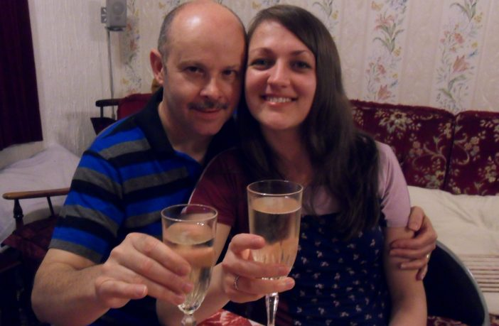 Donna and her husband toasting with a glass of champagne