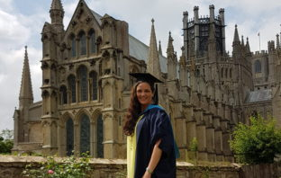Emma Roache stood outside Ely Cathedral in her graduation robes