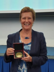 Prof Jean Hartley holding medal