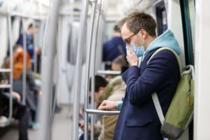 Man on tube with medical face mask
