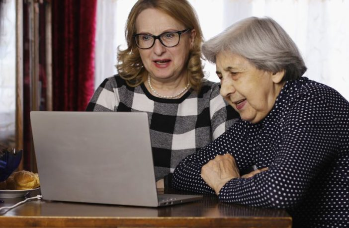Elderly mother and daughter use computer