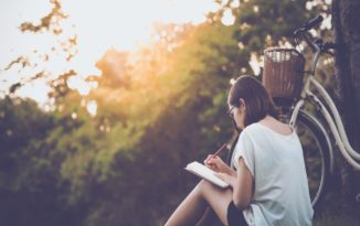 woman sat outside writing in a journal