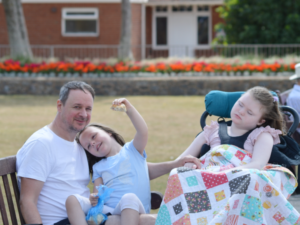 Man sitting on a bench with his two daughters