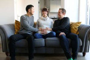 Pregnant woman sitting on sofa with two men either side of her
