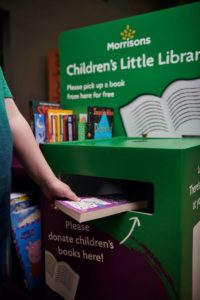 Hand depositing book into the Little Library box