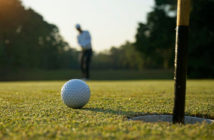 Close-up of a golf ball and a man putting