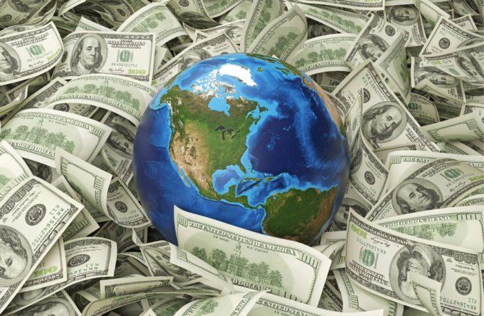 Image of a globe laying amongst dollar notes