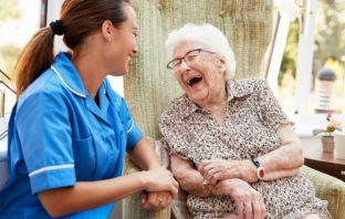 Nurse laughing with an older woman